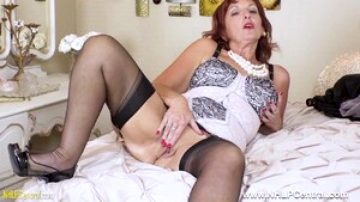 Mature hottie in lacy corset nylons toying pussy