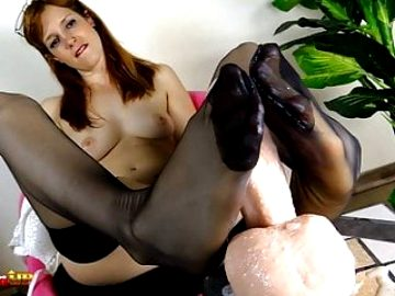 Redhead in stockings sucks her toes and gives a footjob